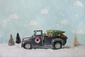 Bottle brush Christmas tree on a toy truck in a winter scene