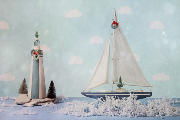 Sailboat and lighthouse with shredded paper water in a Christmas holiday scene