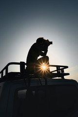 Photographer takes pictures standing on car roof rack. Contre jour picture.
