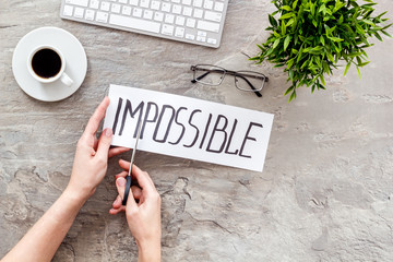 All is possible concept. Hands cut word impossible on grey office desk
