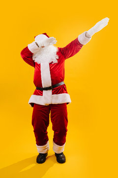 Happy dancing Santa Claus squating and waving hands