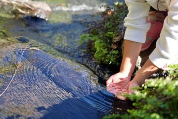 川で水をすくう女の子