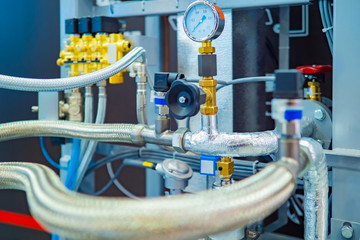 Flexible pipes in a metal braid. Pressure gauge and valves on the pipes. Industrial concept. Fragment of the industrial apparatus. Gas compressor. The production of liquefied natural gas.
