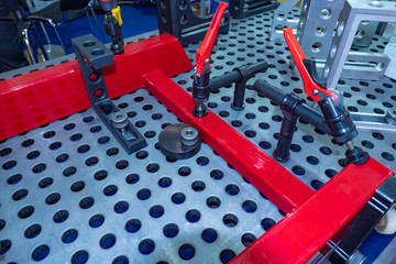 Clamp for fixing metal parts on the mounting table. Fastening of the welded metal product on a special frame. Powerful clamps for metal products. Metalworking.