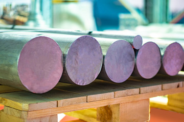 Metal billets lie on pallets. Raw materials for the Metalworking industry. Supply of metals for production. Iron billets of circular cross-section. Nonferrous metal. Metalworking.