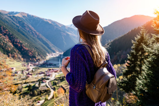 Stylish trendy hipster woman traveler in a felt hat with brown backpack stands on the background of the mountains and uzungol lake in Trabzon during Turkey travel