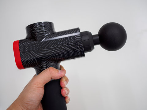 Hand holding a therapeutic massage gun isolated against a white background with copy space