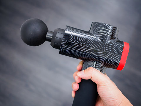 Hand holding a therapeutic massage gun isolated against a dark background with copy space