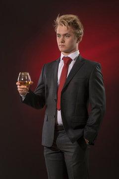Serious young business man raising a glass of cognac