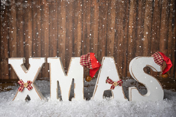The word xmas in wooden letters in the snow