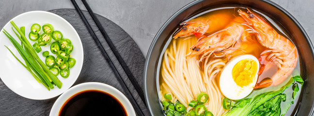 Asian noodle soup, ramen with prawn shrimp, vegetables and egg in black bowl on gray concrete background. Flat lay, Top view, mock up, overhead. Healthy food concept