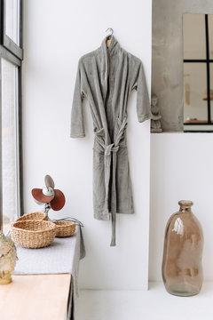 Grey Bathrobe Hang On White Bathroom Wall