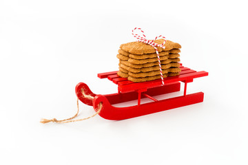 Spekulatius, Speculaas, Speculoos on Red Wooden Sledge isolated on White