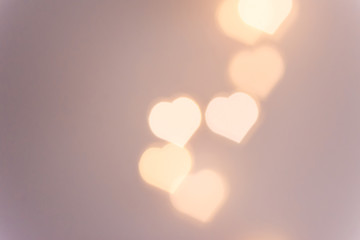 Beautiful pattern from bokeh sparkling garland lights in heart shape on pastel pinkish background. Valentine romantic love charity concept. Copy space