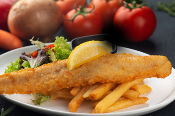 fish and chips with french fries in dark background