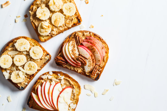 Peanut butter toasts with banana and apple on a gray background, flat lay.