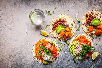 Open vegan tortilla wraps with sweet potato, beans, avocado, tomatoes, pumpkin and  sprouts on gray background, flat lay, copy space. Healthy vegan food concept.