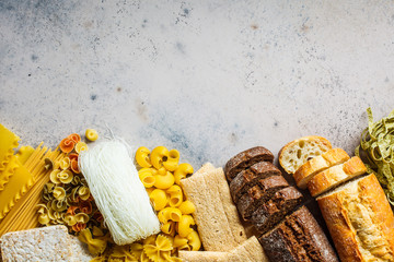 Various pasta background. Bread and different pasta on gray-blue background, copy space, top view.