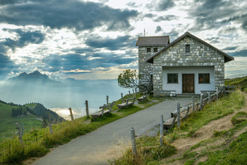 Small chapel with beautiful background with Swiss Alps as seen from top of Mount Rigi