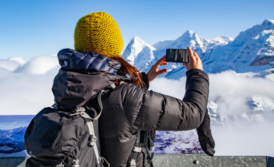 woman traveler in Swiss alps Jungfrau region taking pictures