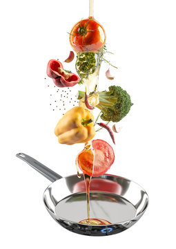 The chrome frying pan with flying colorful fresh vegetables and olive oil. Tomato, pepper, garlic and spices. White isolated background.