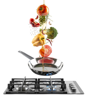 Black Glass gas cooking plate and chrome frying pan with flying colorful fresh vegetables and olive oil. Tomato, pepper, garlic and spices. White isolated background.