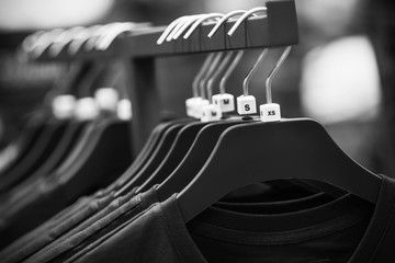 A black-and-white image of hangers hanging in the store, on which hang simple casual t-shirts of different sizes.