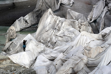 A woman takes a picture of the Ice Cave at the Rhone Glacier at the Furka