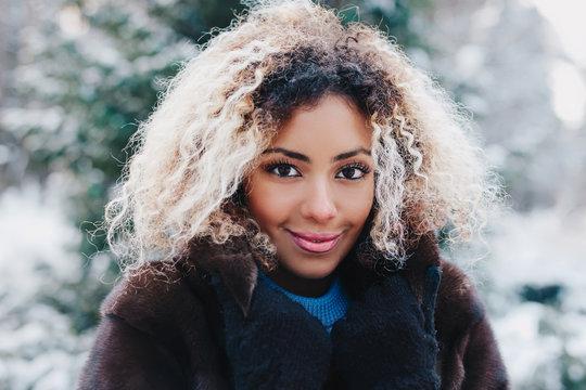Cute afro american girl wearing in fur coat in winter park