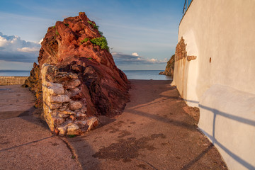 A red rock and a house wall with the sea and clouds in the background, seen in Babbacombe Beach, Torbay, England, UK