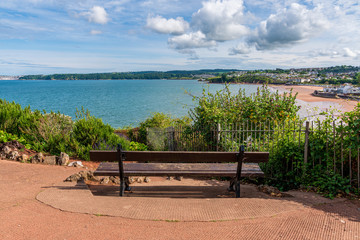 A bench with a view over the Goodrington Sands in Roundham, Torbay, England, UK