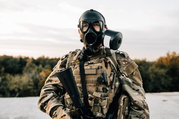 Portrait of a military soldier in a smoke curtain with an assault rifle in a gas mask