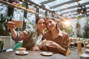 Portrait of two women smiling at smartphone camera while taking selfie photo in outdoor cafe