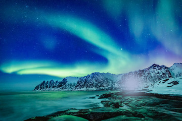 Stores à enrouleur Aurore polaire Vivid Northern lights during polar night on Lofoten Islands in Norway. Epic scene of dancing aurora borealis in the night sky over jagged mountain ridge and Arctic ocean on island Senja, polar circle.