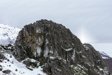 black and vertical rock in the snowy mountain