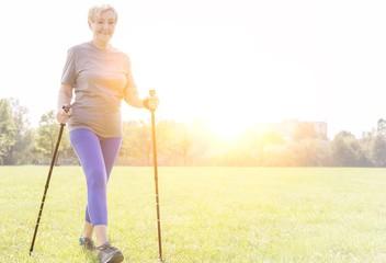 Active senior woman with trekking poles walking in park