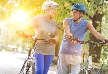 Tilt image of senior couple walking with bicycles in park