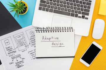 top view of website design template near notepad with adaptive design lettering, laptop, computer...