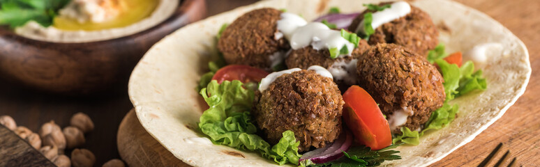 close up view of falafel on pita with vegetables and sauce near hummus on wooden table, panoramic shot