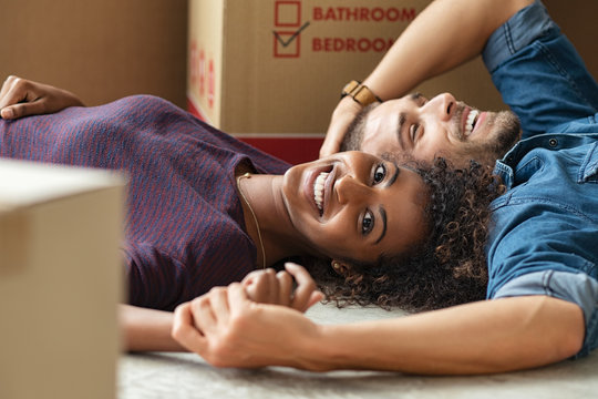 Multiethnic couple lying on floor after moving house