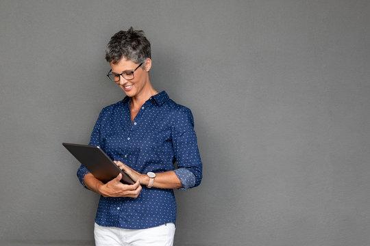 Beautiful mature business woman using tablet