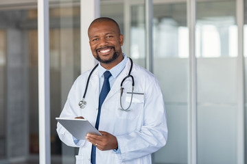 Portrait of happy african doctor at private clinic