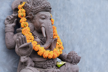 Poster Lieu connus d Asie Ganesha sitting in meditating yoga pose in front of hindu temple. Decorated for religious festival by orange flowers garland, ceremonial offering. Balinese travel background. Bali island art, culture.