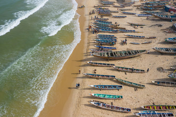 Foto auf Acrylglas Khaki Aerial view of fishing village, pirogues fishing boats in Kayar, Senegal. Photo made by drone from above. Africa Landscapes.