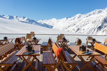 Chairs and Tables on an empty terrace at a ski cafe in an Austrian Resort with Snow capped mountains behind