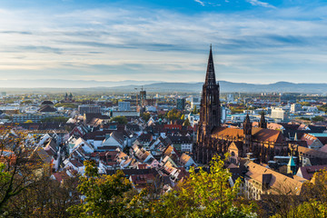 Germany, City freiburg im breisgau skyline with cathedral muenster in old town in warm sunset light in romantic autumn season, aerial view above cityscape