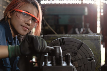 Certified industry female mechanical engineer working on industrial factory machinery - Skilled apprentice technician woman wearing safety equipment - Training, repair and diversity at work concept