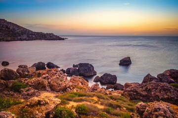 beautiful sunset and seascape view of Golden Bay in Ghajn Tuffieha region, Malta, travel background
