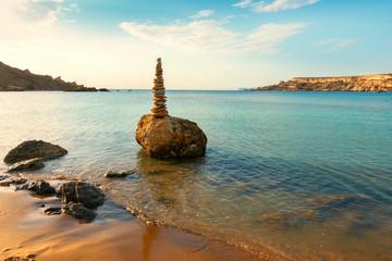 beautiful scene of stones balance on beach, sunrise shot, Malta