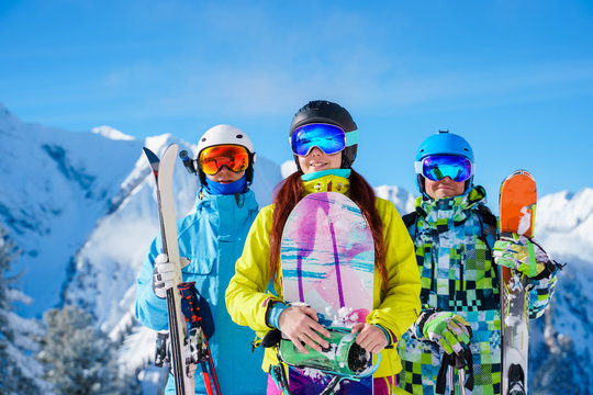 Two men and woman with snowboard and skis standing on snow resort against backdrop of mountain .